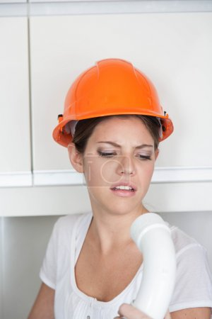 female plumber with pipe