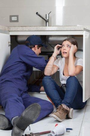 Photo pour Quelques plombiers fixant les tuyaux dans la cuisine - image libre de droit