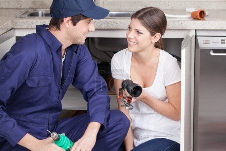 Pair of plumbers with plumbing parts