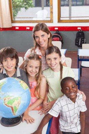 Photo pour Enseignant souriant et élèves en classe de géographie - image libre de droit