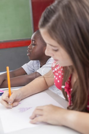 Photo for Pretty girl drawing in classroom - Royalty Free Image