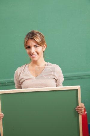 Photo pour Enseignant tenant un tableau noir en classe - image libre de droit