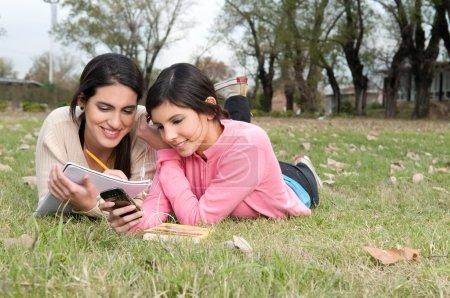 Photo pour Meilleurs amis couchés sur l'herbe étudier - image libre de droit