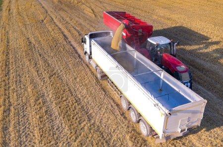 Photo pour Vue aérienne sur la moissonneuse-batteuse remplissant le camion avec les graines de blé - image libre de droit
