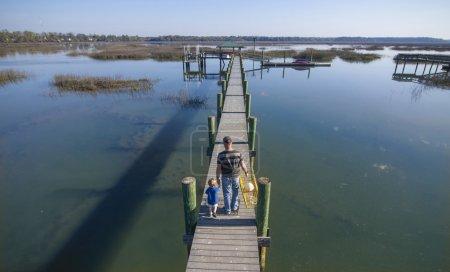 Photo pour Père et fils ou grand-père et petit-fils marchant vers le bas du quai avec le piège de crabe - image libre de droit