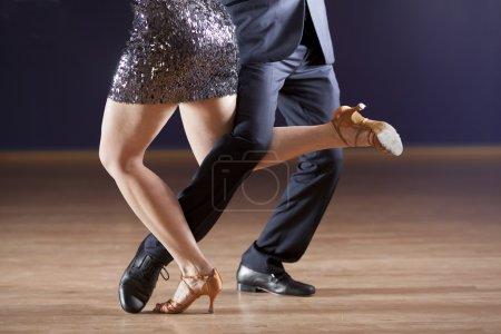Photo pour Couple sexy dansant le tango ensemble en studio de danse avec éclairage dramatique - image libre de droit