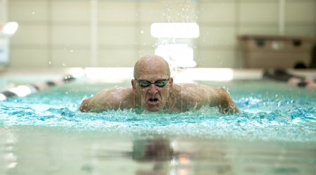 Senior man swimming competitively