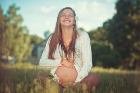 Cute happy Young pregnant woman relaxing at a park