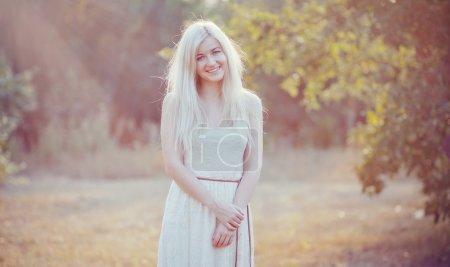 Photo pour Jolie belle jeune femme dans une robe blanche dans un jardin verdoyant, promenades dans le parc summe - image libre de droit