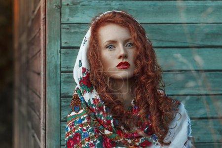 Photo pour Femme rousse Nature Portrait, dans le foulard national. Cheveux longs et courbes. Près des maisons en bois colorées - image libre de droit