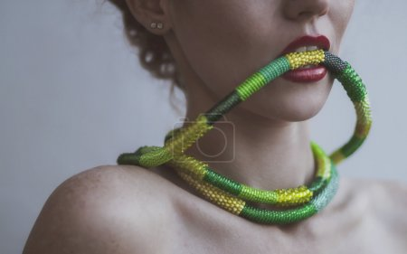 Portrait of a beautiful young woman with a necklace of beads in