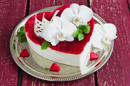 Photo pour Gâteau de fête en forme de coeur avec des fleurs d'orchidée sur un fond en bois. Saint Valentin, fête des mères . - image libre de droit