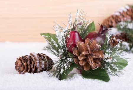 Closeup of a Christmas ornament on snow with wooden background