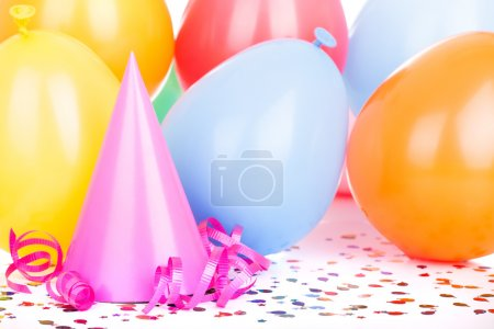 Photo pour Pink birthday party hat with balloons in background - image libre de droit