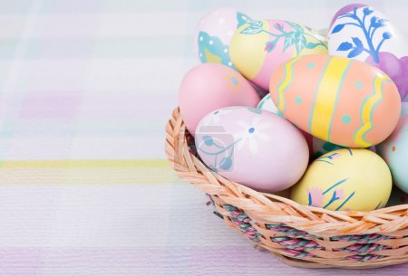 Photo for Basket of colorful Easter eggs on a pastel colored surface - Royalty Free Image