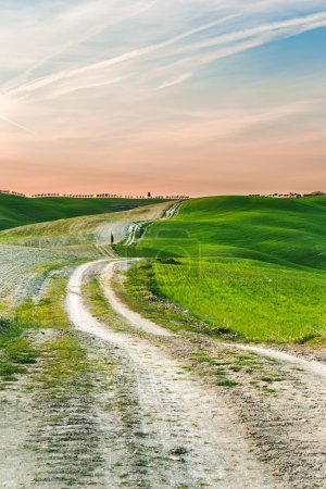 Long and winding rural road crosses the hills at sunset