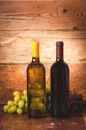 Red and white wine bottle with grapes and barrel on wooden rusti