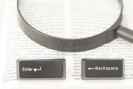 Enter and Backspace Computer Keys and a Lens on a Book Page