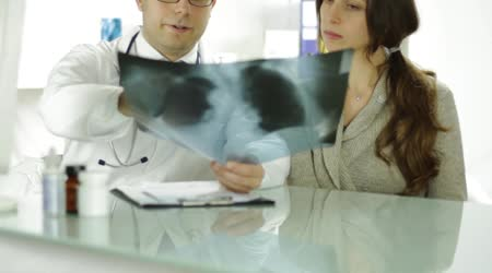 Doctor and Patient Looking at Xray Writing Prescription