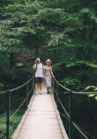 Hipster couple hiking on the background of a natur...
