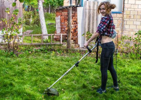 Woman in Plaid Shirt Mowing Lawn