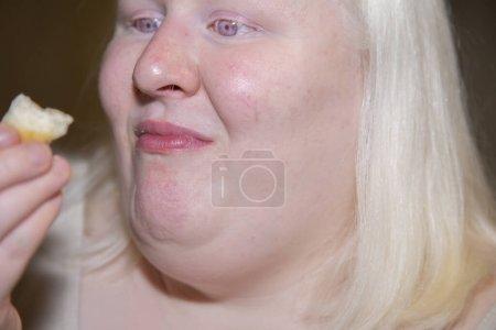 Mujer que está llena todavía comiendo una galleta de suero de leche