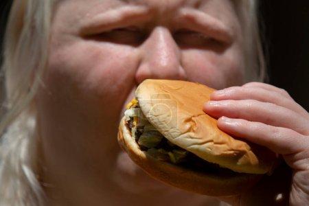 Mujer albina comiendo una hamburguesa doble de queso de carne