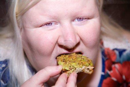 Mujer felizmente comiendo un pedazo de pan tostado de aguacate