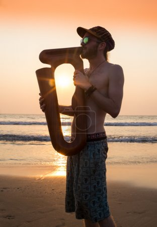 Dj playing summer hits at sunset beach party with trumpet jazz performer