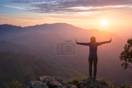 Photo for Happy celebrating winning success woman at sunset or sunrise standing elated with arms raised up above her head in celebration of having reached mountain top summit goal during hiking travel trek - Royalty Free Image