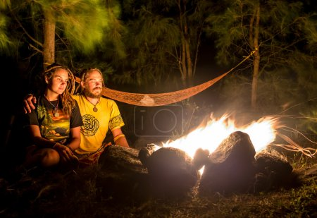 Campfire on a rocky beach with couple sitting