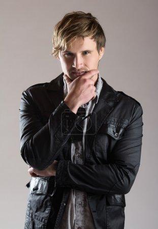 Photo pour Portrait d'un bel homme caucasien blond portant une chemise à bouton bleu délavé et une veste noire en cuir . - image libre de droit