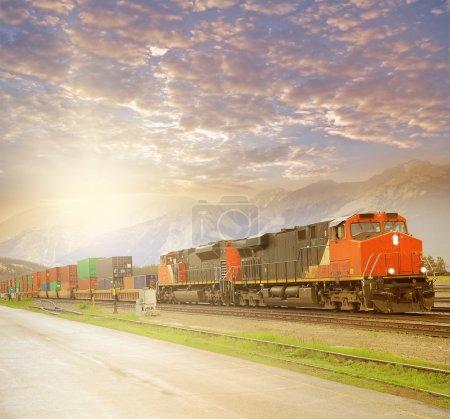 Photo pour Train de marchandises dans les rochers canadiens au coucher du soleil. Jasper. Alberta . - image libre de droit