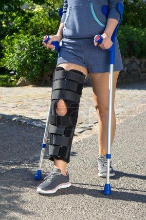 Woman wearing a leg brace walking on crutches.