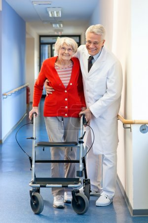 Physician helping a senior woman in a walker.
