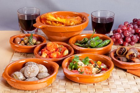 Spanish tapas foods in terracotta bowls