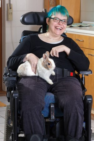 Photo for Cheerful young infantile cerebral palsy patient sitting in multifunctional wheelchair and stroking pygmy rabbit as therapy - Royalty Free Image