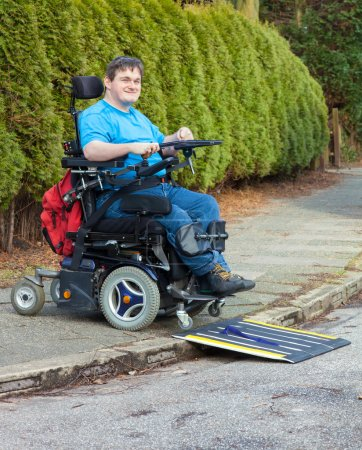 Foto de Spastic young man with infantile cerebral palsy using mobile ramp on kerb to drive onto road with multifunctional wheelchair - Imagen libre de derechos