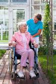 Starší paní na vozíku s péči asistent