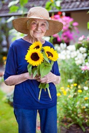Senior Woman Holding Sunflowers