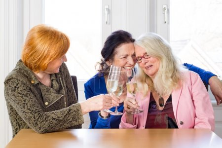 Photo for Three Happy Middle Age Best Friends Tossing Glasses of White Wine, sitting at Wooden Table Inside Restaurant - Royalty Free Image