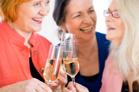 Photo for Close up of Three Happy Adult Women in Trendy Attire Tossing Glasses of White Wine While Laughing at Something - Royalty Free Image