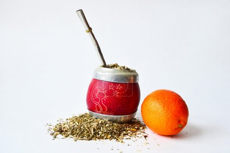 Hand-made mate cup full of guarana, metallic tube for drinking and a mandarin