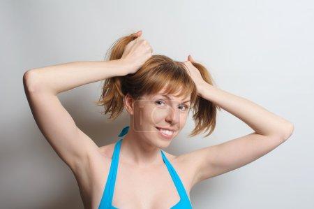 Joyful girl playing with hair