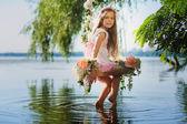 Dívka na houpačce přes řeku