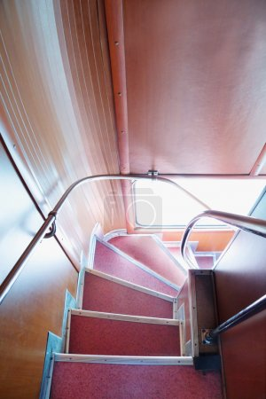 Descend down angular stairway in English double-decker bus