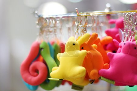 Small soft multicolored bunnies and snakes keychains hang in sho