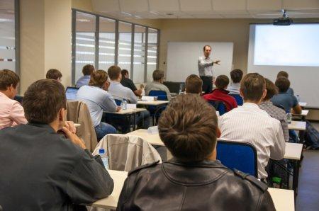 Photo pour Vue arrière des personnes assises dans la classe près de la table et écoutant la présentation - image libre de droit