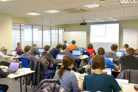 Photo pour Personnes assises arrière à la classe de formation informatique - image libre de droit