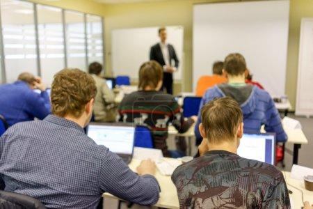 Photo pour Les gens assis à l'arrière à la classe de formation informatique - image libre de droit